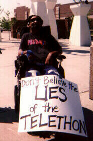 "Photo of protester with sign saying ""Don't Believe the Lies of the Telethon""; click to hear activists' response"